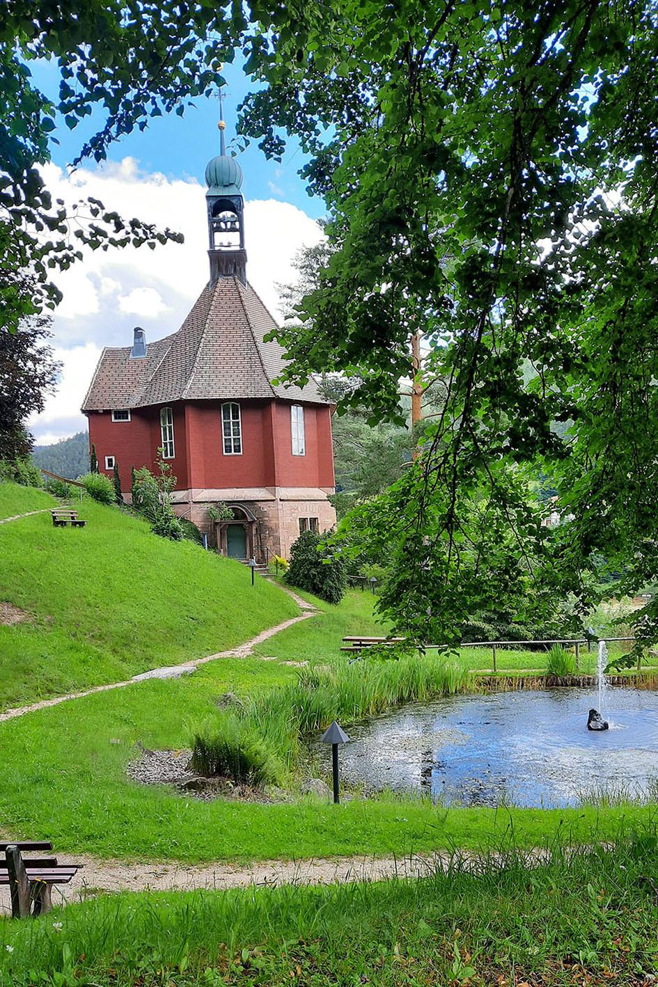 Die rote Michaelskirche in Baiersbronn mit einem kleinen Teich, liegt direkt am Waldrand.