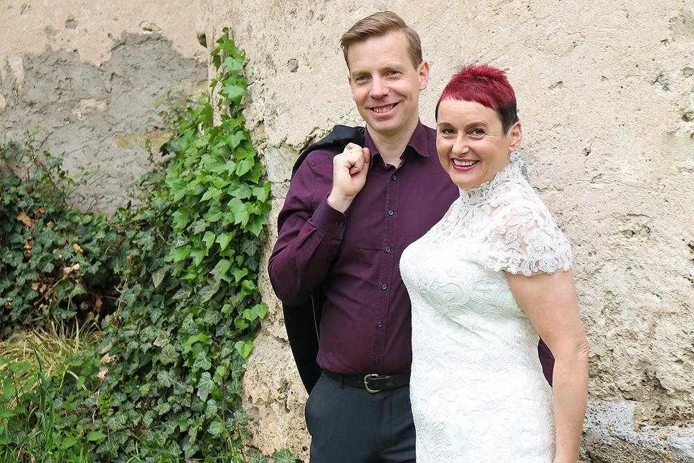 Bräutigam und Braut stehen an einer Mauer. An der Wand wächst Efeu.