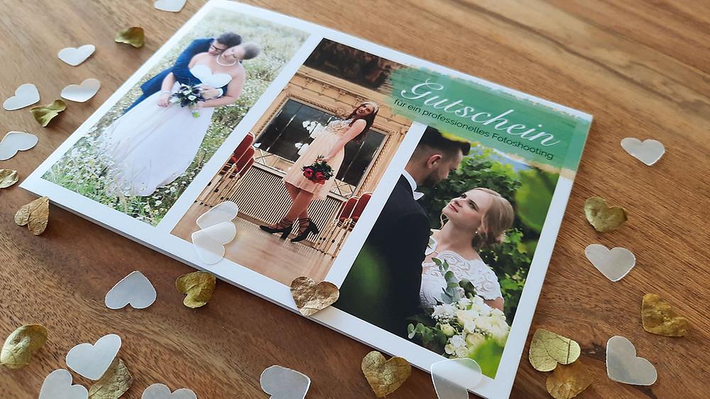 Der Ohana Photography Fotografie Gutschein liegt auf einem Tisch mit Herzen aus Blättern und Papier.