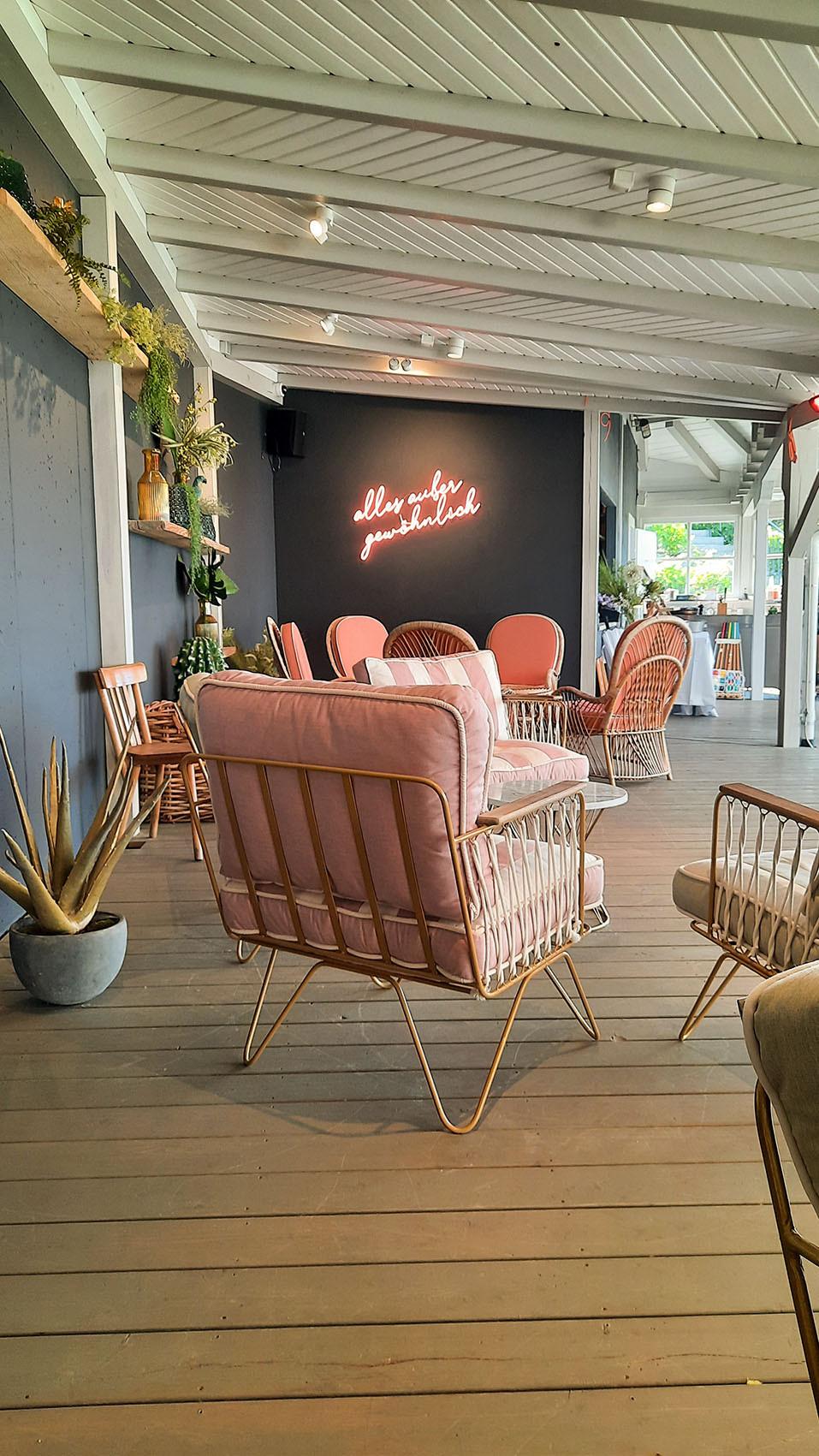 Loungemöbel und Neonschrift unterm Holz-Pavillon.