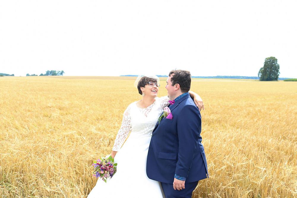 Brautpaar Inge und Benjamin schauen sich verliebt an. Sie stehen in einem Weizenfeld in Berghülen bei Blaubeuren. Fotoaufnahme von Ohana Photography.