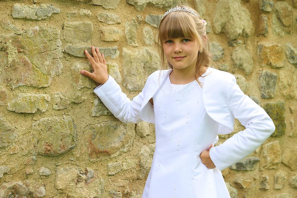 Alina steht in ihrem weißen Kommunionskleid an der Kirchenmauer in Horb-Nordstetten.