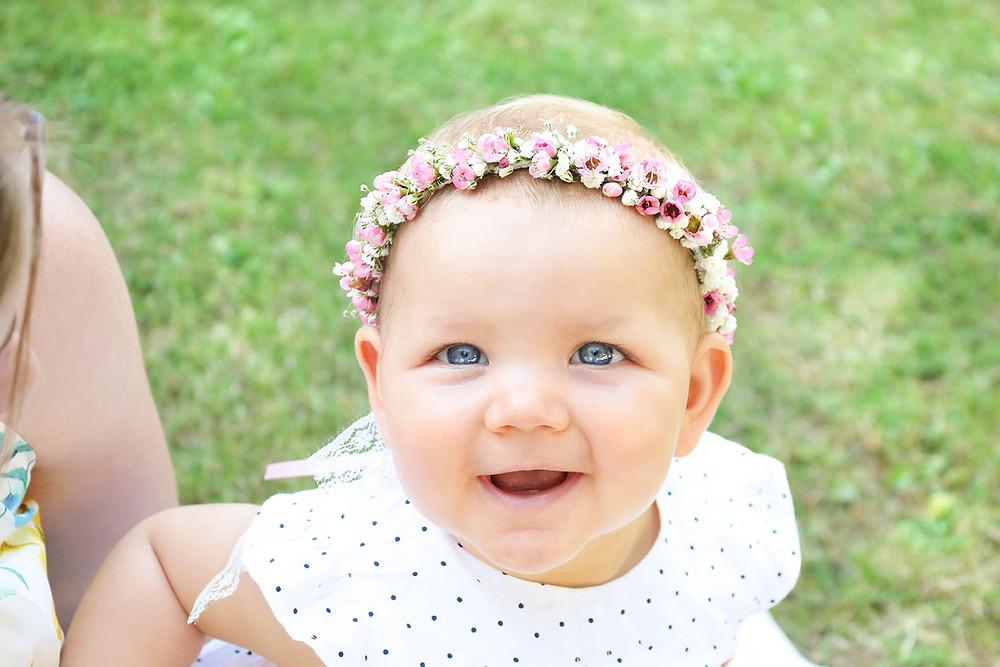 Täufling Henriette lächelt in die Kamera. Auf dem Kopf trägt sie einen Blumenkranz.