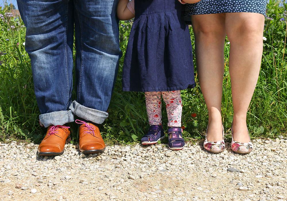 Schuhe von Papa, Kind und Mutter.