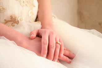 Die Hände der Braut ruhen im Schoß. Sie trägt einen funkelnden Ehering.