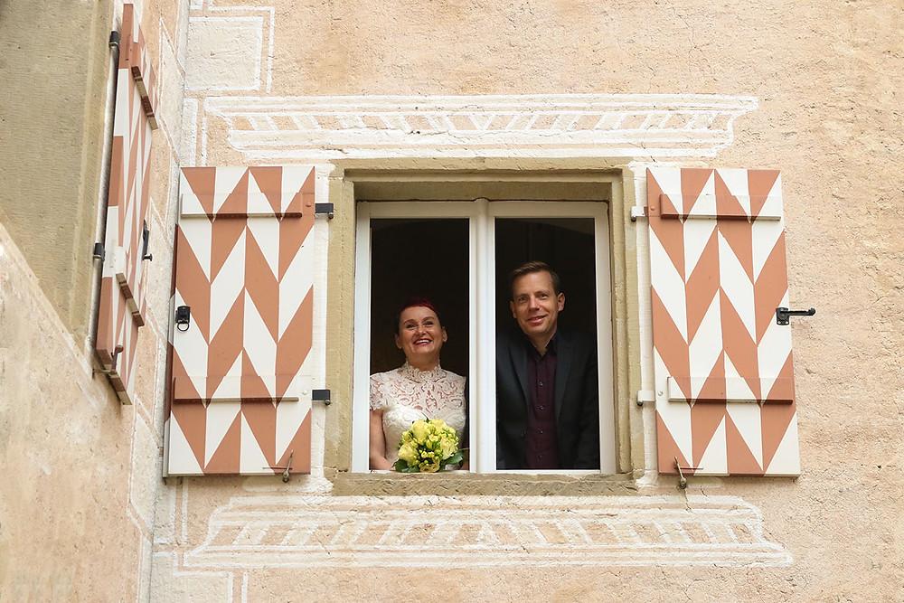 Das Brautpaar blickt aus einem Fenster in den Innenhof. Die Fensterklappen sind bunt angemalt.