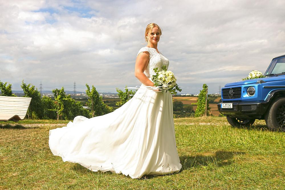 Die Schleppe des weißen Brautkleides wirkt schwebend. Im Hintergrund steht das Hochzeitsauto.