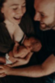 Mamma som ammer sitt nyfødte barn og skratter samme med mannen sin. Av Maria Hilebrand ved Born Wild Photography