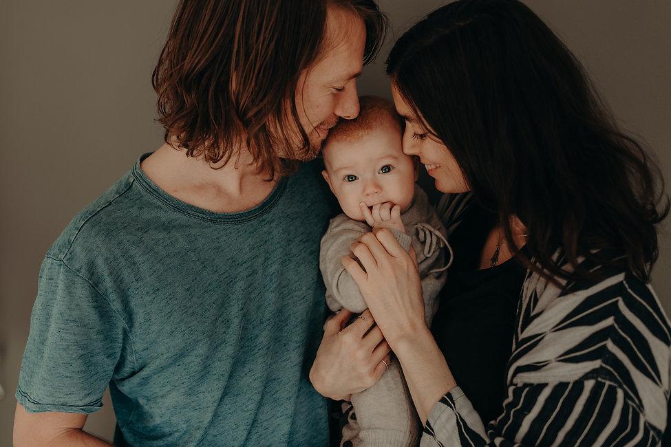 Mamma, pappa og barn omfavner hverandre. Familiefotografering. Born Wild Photogra