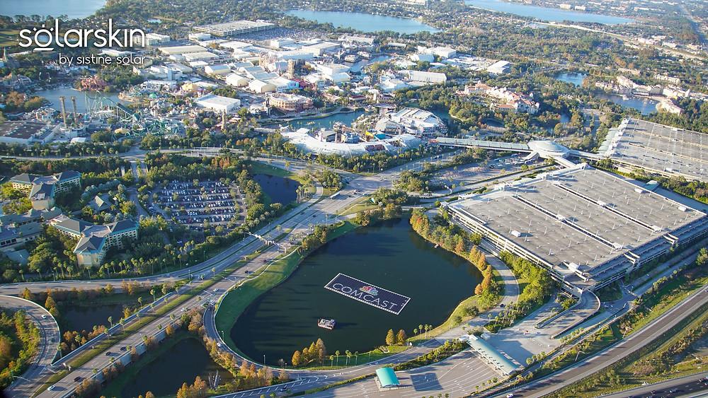 Comcast logo design across SolarSkin on floating solar array at Universal Studios Orlando