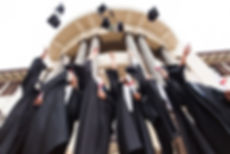 group of happy graduates throwing gradua