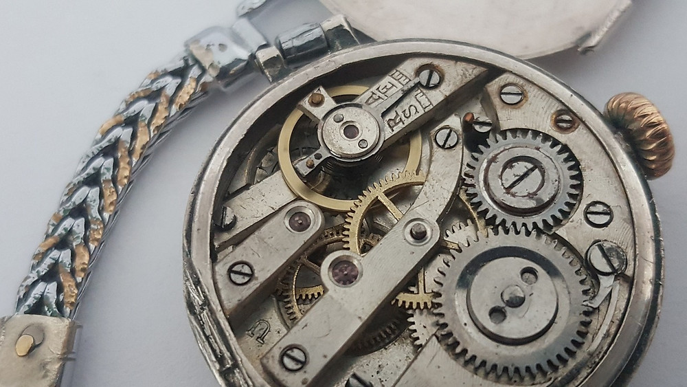 [Image description] An old mechanical watch with it's gears showing
