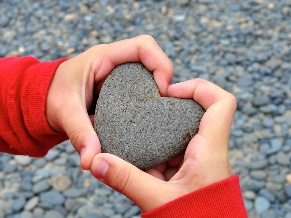 A person makes a heart with their fingers around a heart-shaped rock