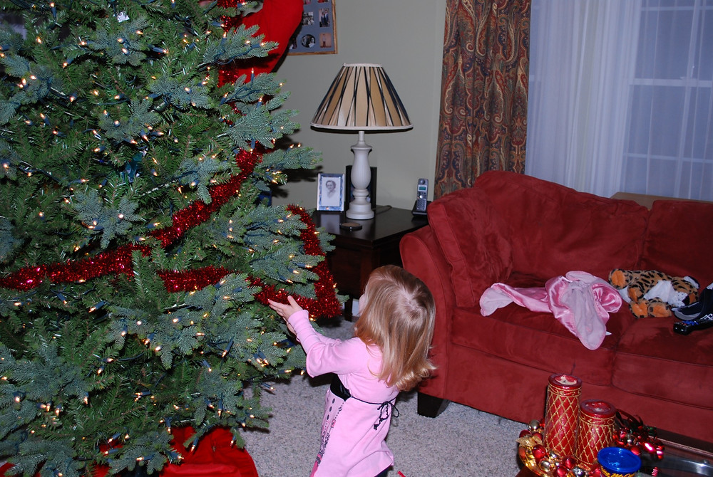 Young girl child helping decorate Christmas tree