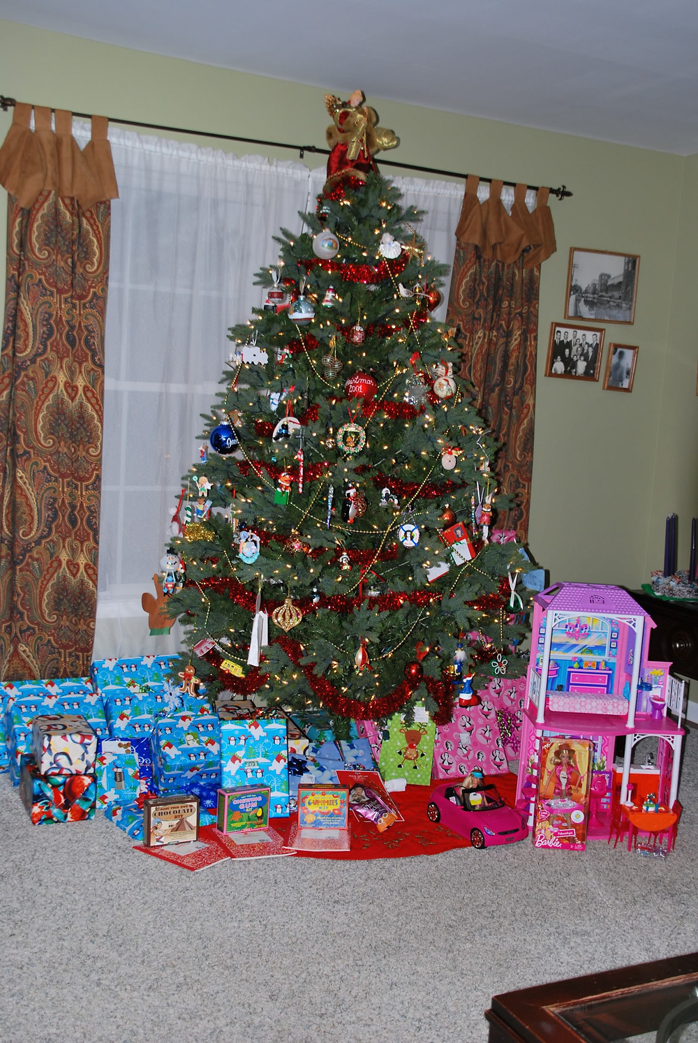 Christmas tree with wrapped presents, science games, and Barbie house and car