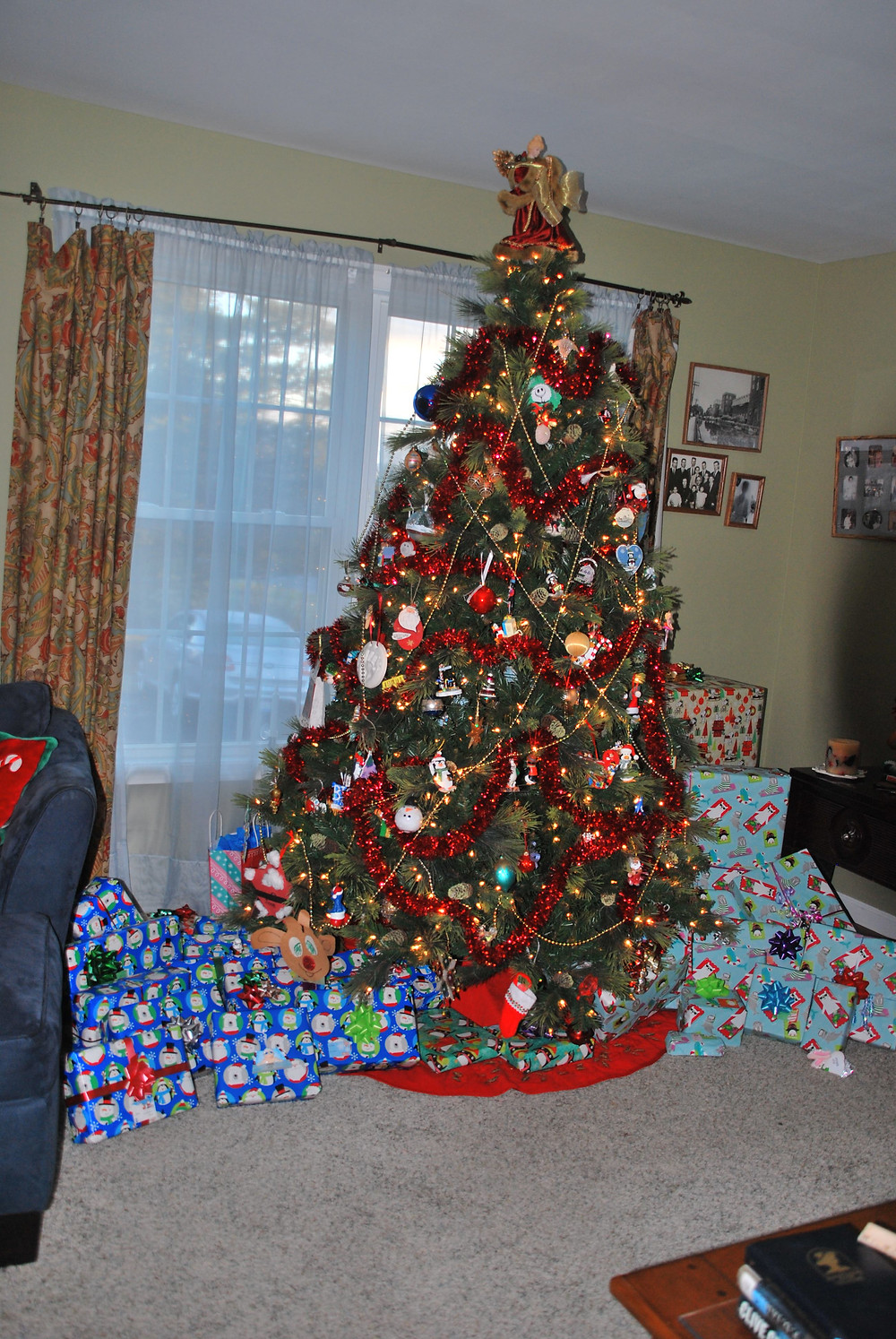 Christmas tree with a pile of presents wrapped in blue and a pile of presents wrapped in aqua