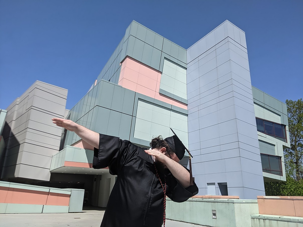 Chris in his cap and gown dabbing