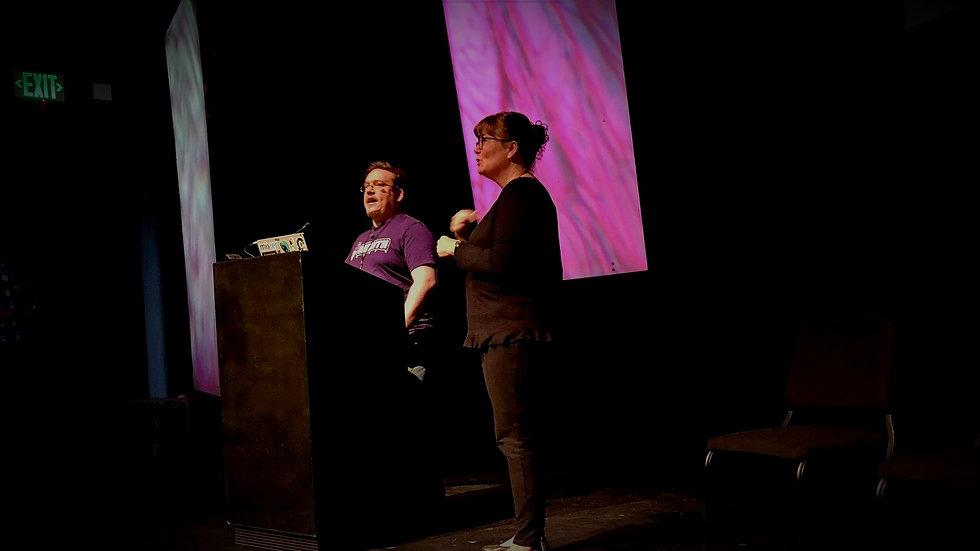 Jay Kidd and an ASL interpreter giving a talk at GAconf in 2019