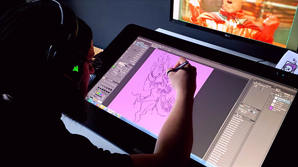 Lance T. Miller drawing concept art for Wraith mascot Yorick on his Cintique tablet