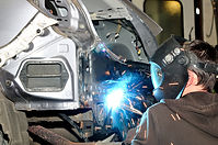 Body shop worker welding car panel..jpg