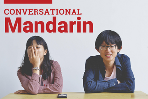 Chinese woman and man grinning at the start of a conversation