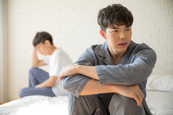 Asian gay couple sitting on a bed  argui