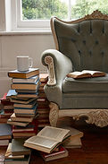 coffee cup on pile of books beside chair