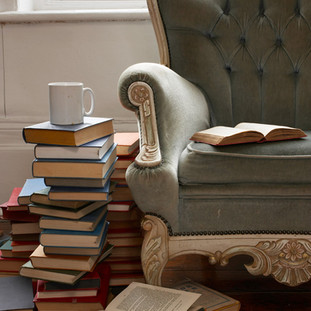 Stack of books next to High back chair