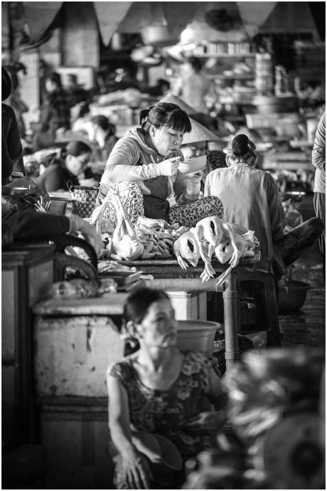 Vietnamese woman eating noodles at farmers market