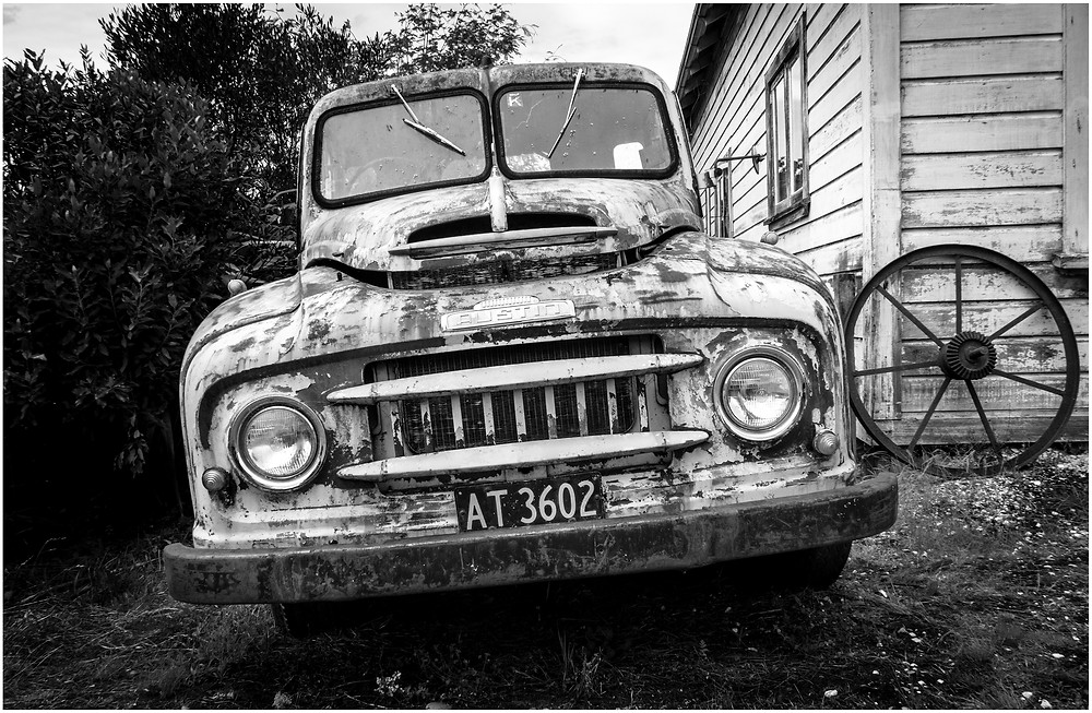 rusty old american pickup truck sitting outside a farm house in rural new zealand