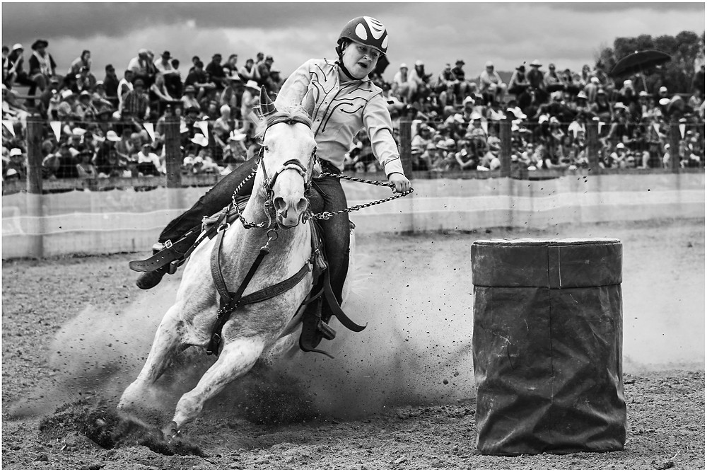 Cowgirl slides her white horse around a barrel during a barrel race at the New Zealand Summer rodeo