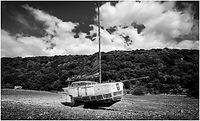 art boat on rocky beach