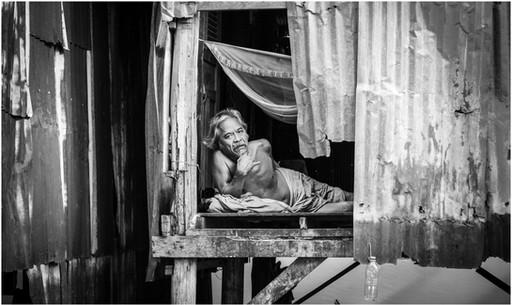 Old man sleeping in slum hut
