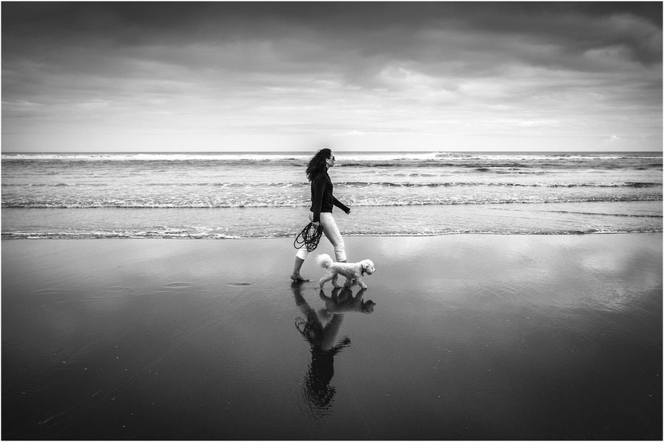 Woman walking dog on a wild West Coast beach during storm...