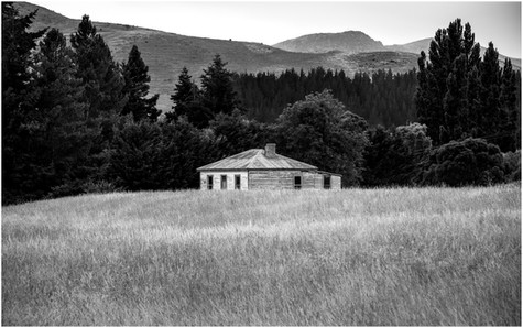 Abandoned farmhouse in grassy field landscape...