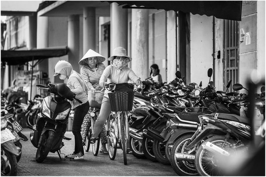 Vietnamese girls on bikes at market