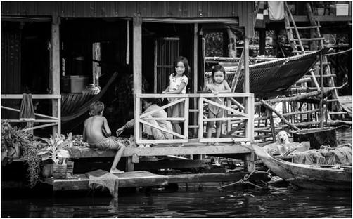 Kids on porch, wet season, Central Cambodia