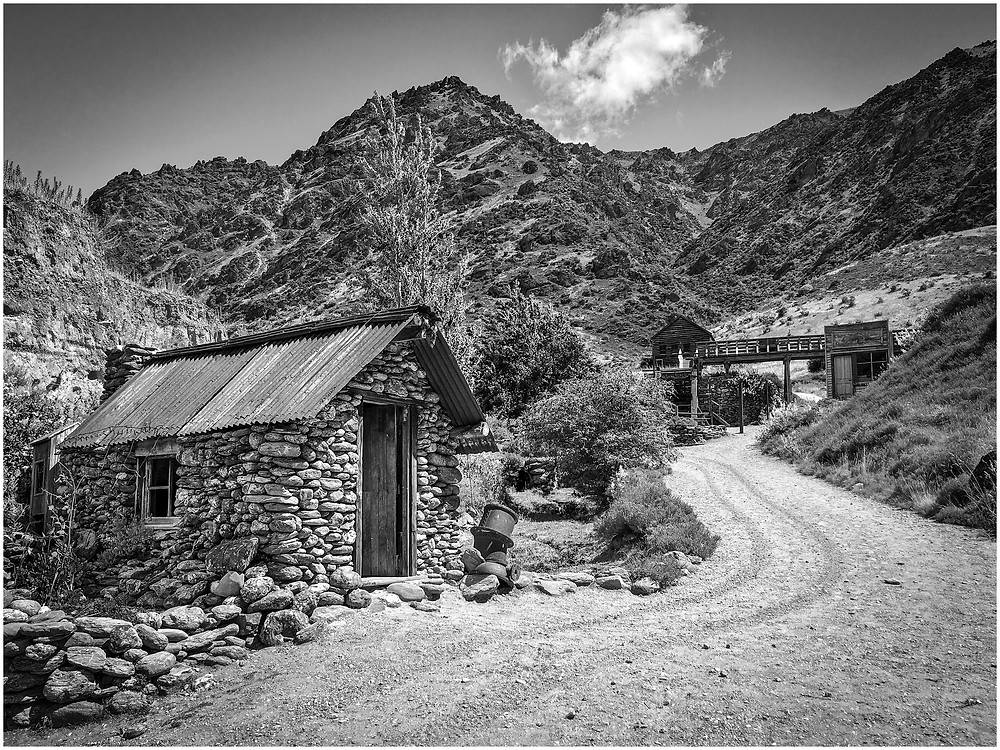 Stone huts and abandoned buildings at an abandoned gold mine in the hills of Central Otago, New Zealand