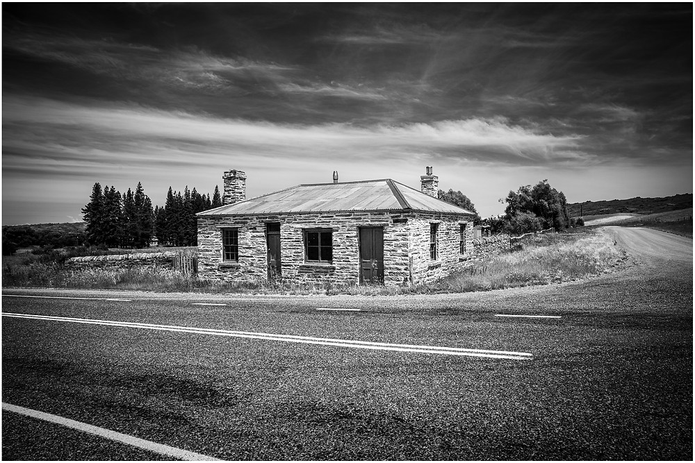 abandoned early settler stone house on the edge of the main highway
