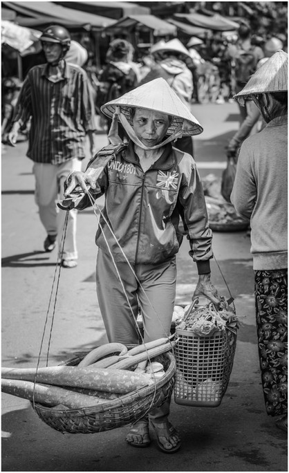 Vietnamese man carring produce to market