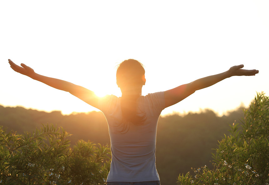 thankful woman open arms to the sunrise