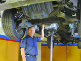 Inspecting the powertrain under the truck.