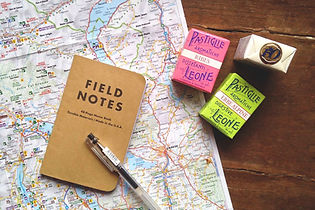 map notebook ink pen candy on table
