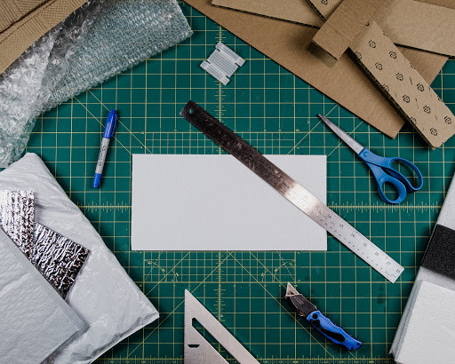 cardboard, ruler, marker, scissors, paper, bubble-wrap, angle, exacto knife, architecture and other engineering tools.