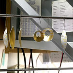Jewelry pieces drying on a rack