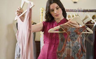Femme hésitant entre 2 robes sur des supports