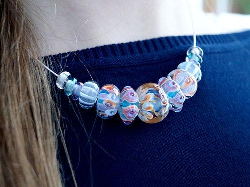 Collier mit hellblau und rosa gemusterten Perlen