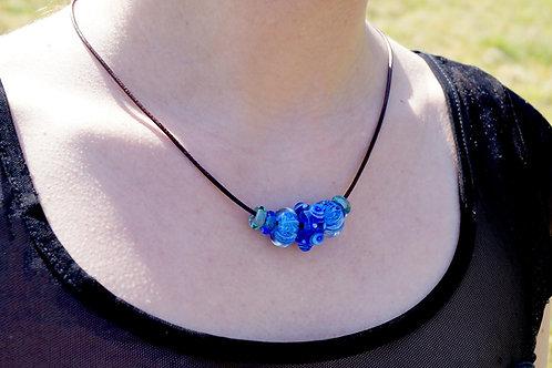 Blau gemusterte Perlen auf Lederkette