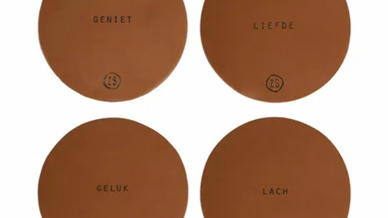 Set van 4 lederen onderzetters met tekst - bruin