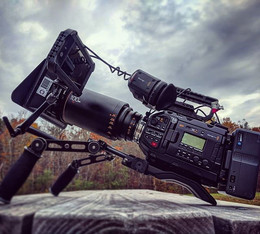 An anamorphic camera set up under clouds